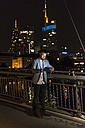 Young man with tablet and earphone on urban bridge at night - UUF10903