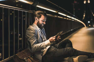 Smiling young man with tablet and earphone sitting on bridge at night - UUF10906
