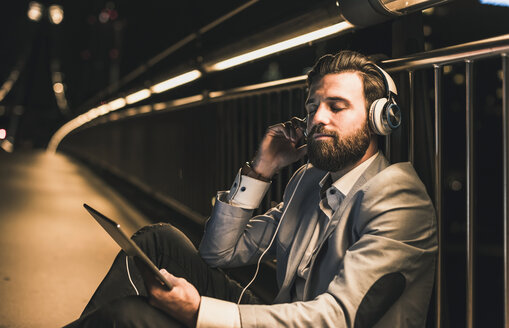 Young man with tablet and headphones sitting on bridge at night - UUF10909
