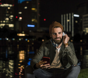Stylish young man with cell phone and headphone sitting at urban riverside at night - UUF10912