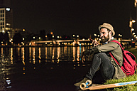 Smiling young man with cell phone and skateboard sitting at urban riverside at night - UUF10915