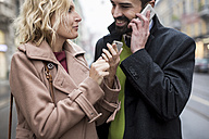 Happy business couple with cell phones in the city - MAUF01102