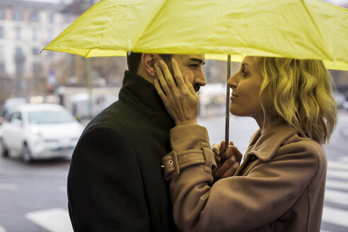 Affectionate business couple under umbrella in the city - MAUF01108