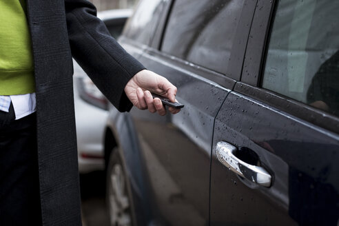 Close-up of businessman opening car with remote control - MAUF01114