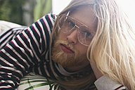 Portrait of bearded young man with long blond hair wearing spectacles - RTBF00954