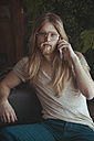 Portrait of young man with long hair and beard using smartphone at home - RTBF00957