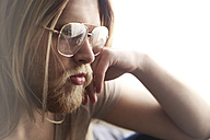 Portrait of pensive young man with long blond hair wearing spectacles - RTBF00960