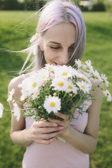 Happy woman holding bunch of daisies - GIOF02821