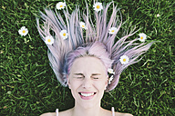 Portrait of woman lying on grass with eyes closed and daisies on hair - GIOF02836
