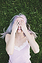 Laughing woman lying on grass covering eyes with her hands - GIOF02839