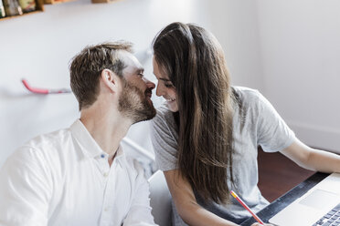 Happy couple with laptop at home kissing - GIOF02847
