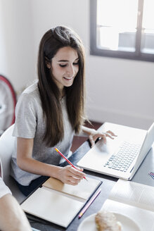 Smiling woman at home using laptop taking notes - GIOF02850