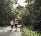 Two women running on country road - UUF10916