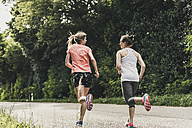 Two women running on country road - UUF10919
