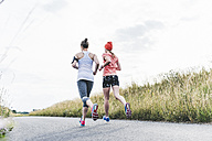 Two women running in the countryside - UUF10922