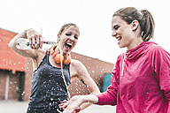 Two playful women with water bottle having a break from exercising - UUF10931