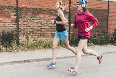 Two women running on the street - UUF10934