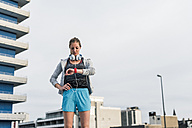 Woman having a break from exercising looking at smartwatch - UUF10937