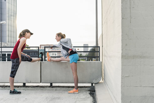 Two active women stretching in the city - UUF10940