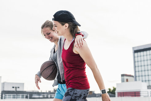 Two happy women with basketball in the city - UUF10943