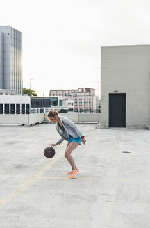 Woman playing basketball on parking level in the city - UUF10946