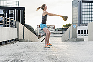 Woman exercising with kettlebell on parking level in the city - UUF10949