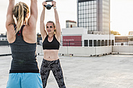 Two women exercising with kettlebells on parking level in the city - UUF10952