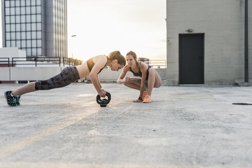 Woman cheering at training partner kettlebell on parking level in the city - UUF10955