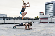 Two women exercising on parking level in the city - UUF10964