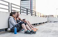Two women having a break from exercising sharing smartphone - UUF10967