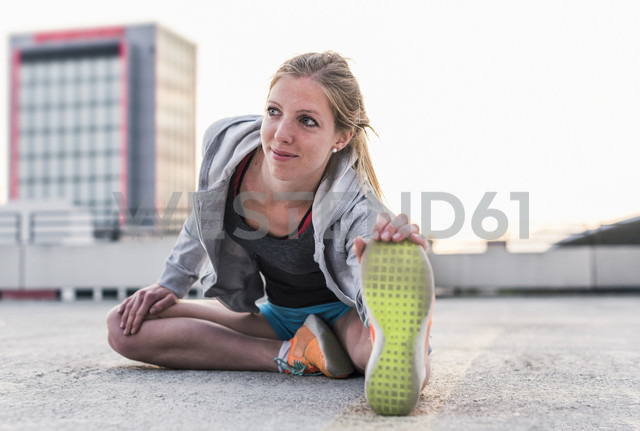 Active woman stretching on parking level in the city - UUF10970