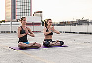 Two women practicing yoga on parking level in the city - UUF10973