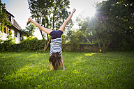 Back view of girl turning cartwheel on a meadow - LVF06207