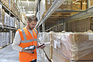 Man in factory hall wearing safety vest holding clipboard and barcode scanner - LYF00737