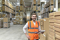 Portrait of smiling man in factory hall wearing safety vest holding clipboard - LYF00743