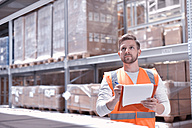 Man in factory hall wearing safety vest holding clipboard - LYF00755