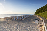 Germany, Ruegen, Sellin, view to beach with hooded beach chairs at morning twilight - ASCF00759