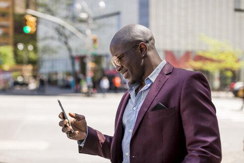 Stylish businessman looking at smartphone - MAUF01135