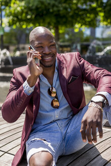 Portrait of smiling businessman on the phone - MAUF01138