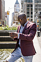 USA, New York City, Manhattan, stylish businessman looking at smartphone - MAUF01141