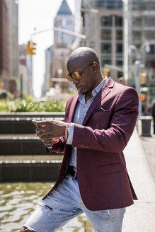 USA, New York City, Manhattan, stylish businessman looking at smartphone - MAUF01141