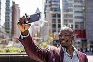 USA, New York City, Manhattan, stylish businessman taking selfie with smartphone - MAUF01144