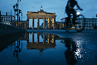 Germany, Berlin, view to  Brandenburg Gate reflecting in puddle by night - ZMF00485