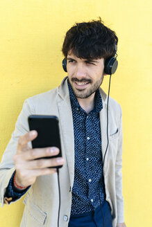 Portrait of young man with headphones and cell phone - GIOF02878