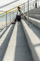 Pensive man sitting on steps outdoors - GIOF02884