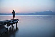 Italy, Lazise, man standing on jetty looking at Lake Garda - IPF00392