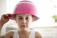 Portrait of serious little girl with pink mixing bowl on her head - MOEF00024