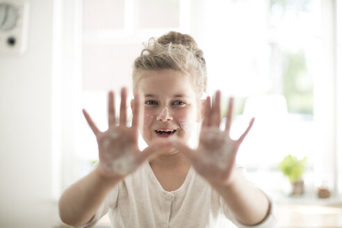 Portrait of smiling girl in the kitchen with dough on hands and face - MOEF00045