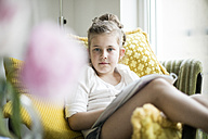 Portrait of relaxed little girl sitting with magazine on armchair - MOEF00048