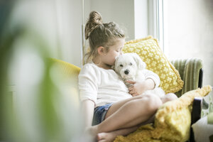 Little girl sitting on armchair at home cuddling with her dog - MOEF00054
